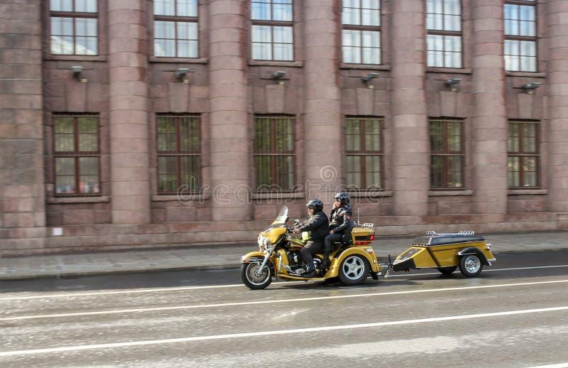 Un couple montant un tricycle avec une remorque image libre de droits