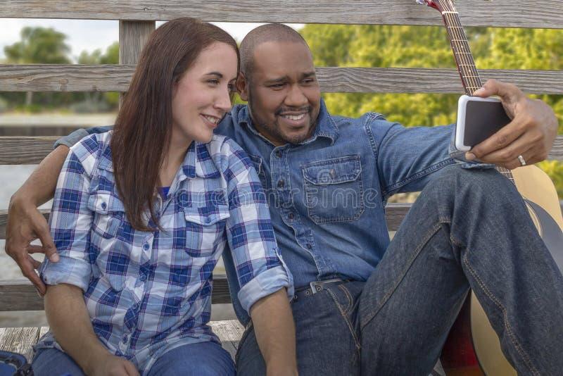 Un couple multiracial se repose sur une plate-forme avec le smartphone photos stock