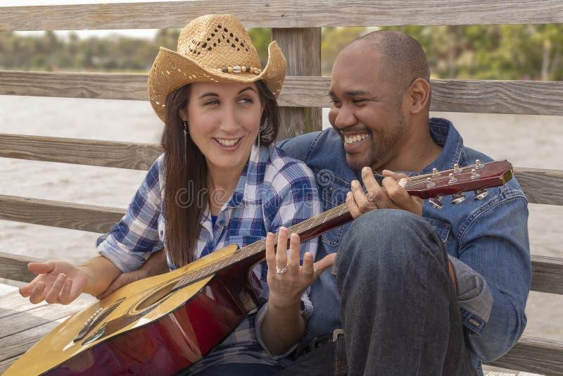 Un couple multiracial se repose sur une plate-forme riant fort photos stock
