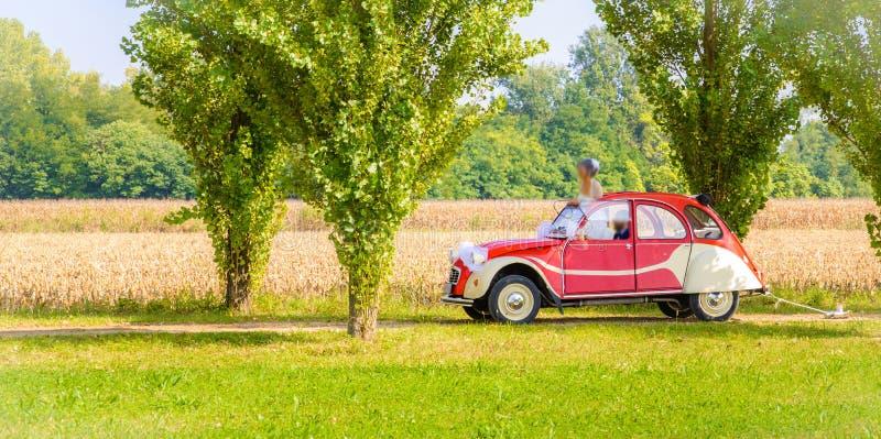 Un couple non identifiable de nouveaux mariés conduit une rétro voiture sur une route de campagne pour leur lune de miel photos libres de droits
