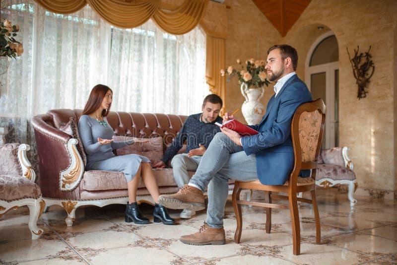 Un couple parlant sur le divan à un psychologue photos stock