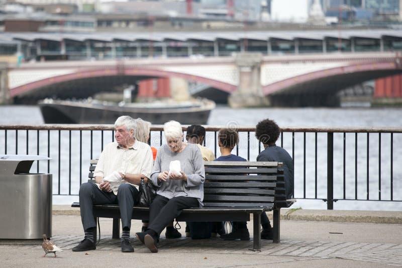 Un couple plus âgé mangeant du maïs éclaté, se reposant sur un banc donnant sur la Tamise Rivage du sud de la Tamise photo libre de droits