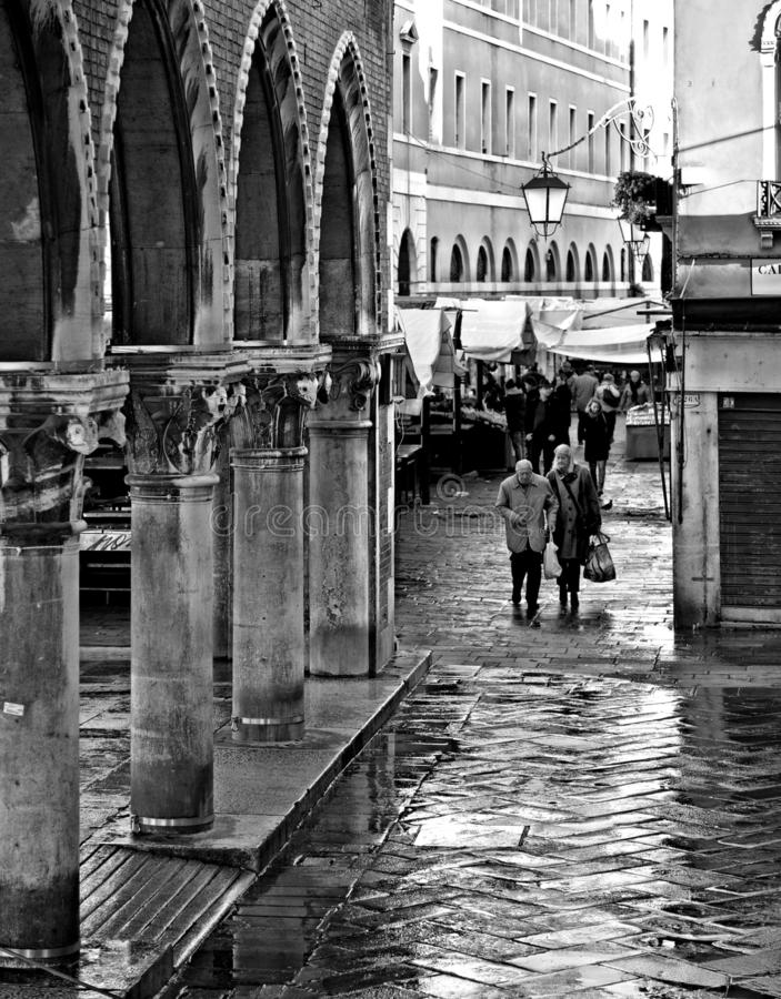 Un couple plus âgé marchant sur les rues humides de Venise près du pont de Rialto et des arcades de la poissonnerie l'Italie images stock