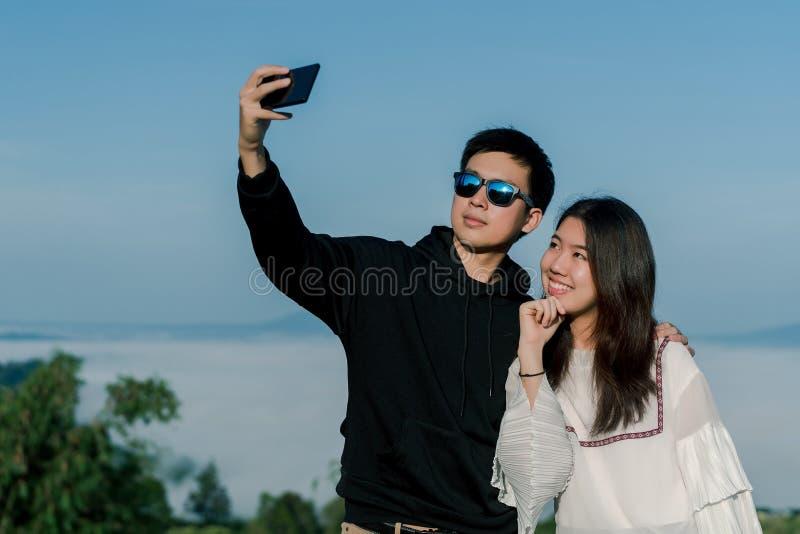 Un couple qui sont des amants sur dater prend des selfies ensemble par le smartphone avec la vue supérieure de la colline dans le images libres de droits