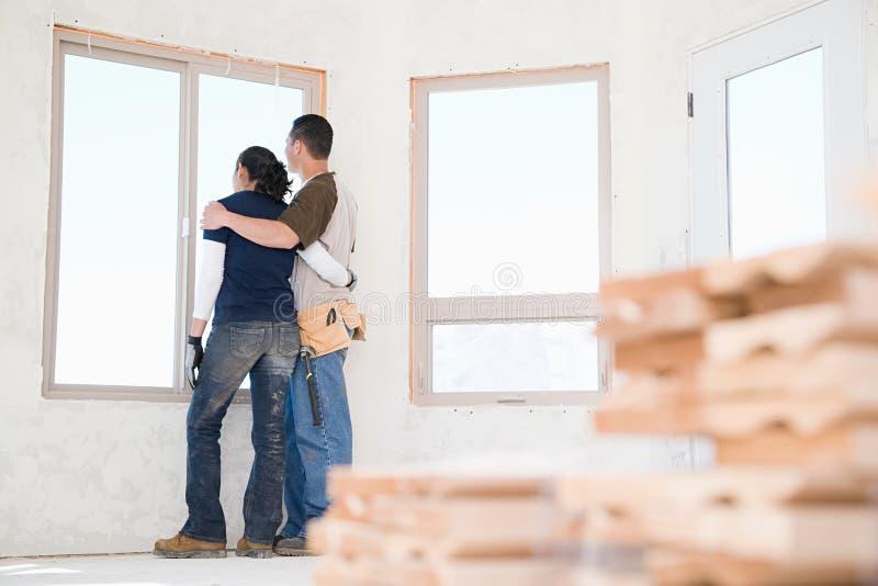 Un couple regardant hors d'une fenêtre de leur nouvelle maison image stock