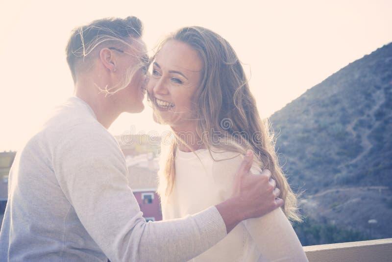 Un couple romantique flirtant en plein air avec le coucher du soleil et la vue sur la ville - l'amour des jeunes hommes et femmes  photographie stock