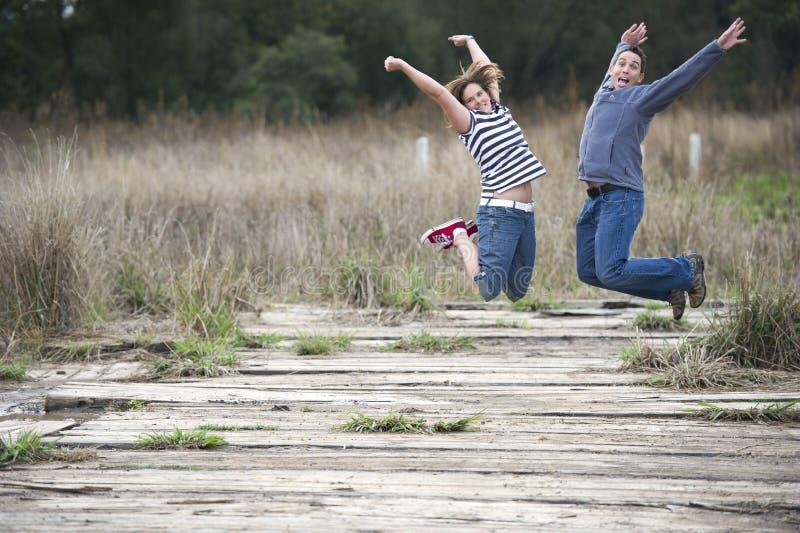 Couples heureux sautant dehors image stock