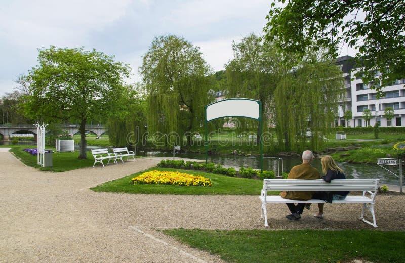 Un couple se reposant en parc avec un signe vide devant eux image stock