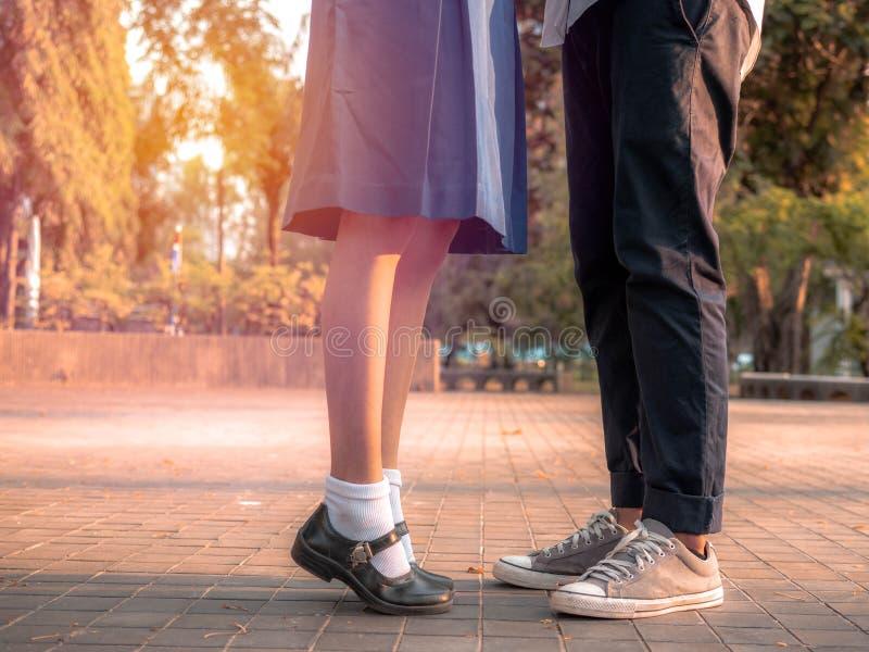 Un couple se tenant ensemble, jambes et espadrilles des couples dans l'uniforme scolaire se tenant en parc, embrassement de coupl images libres de droits
