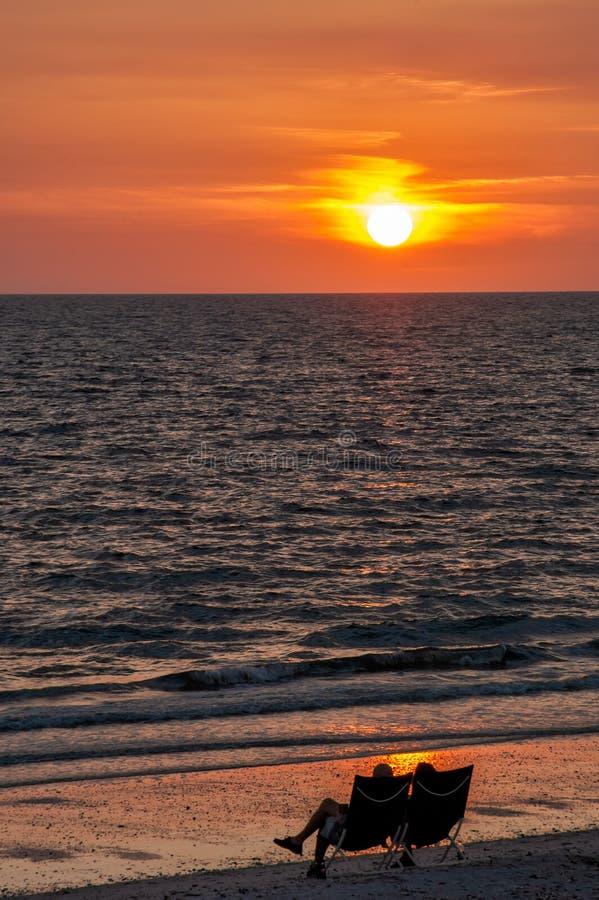 Un couple silhouetté observe le coucher du soleil à la plage photos stock