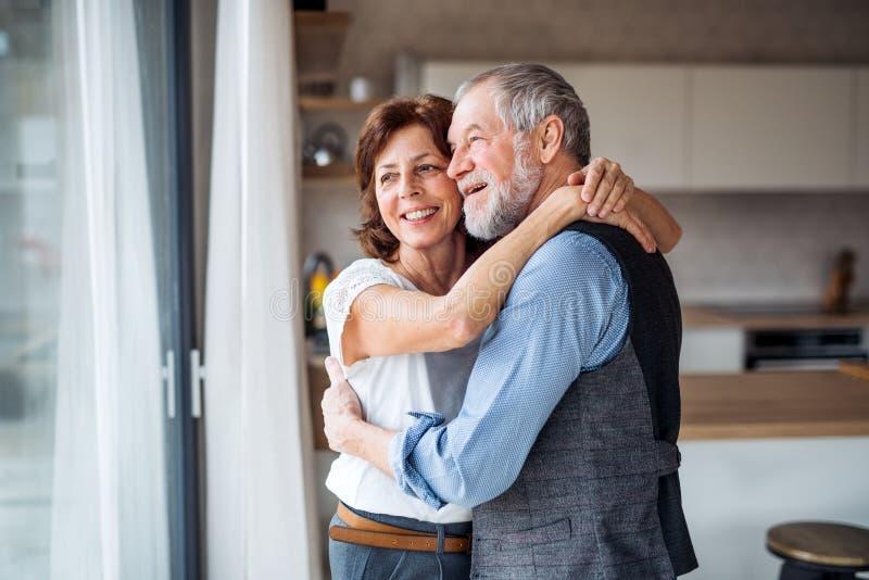 Un couple supérieur à l'intérieur à la maison, regardant hors de la fenêtre image libre de droits