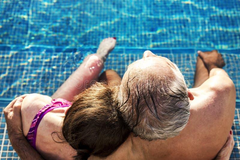 Un couple supérieur étreignant dans la piscine photos stock