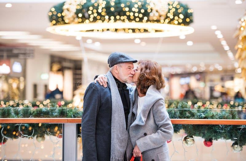 Un couple supérieur heureux se tenant au centre commercial, embrassant photo stock