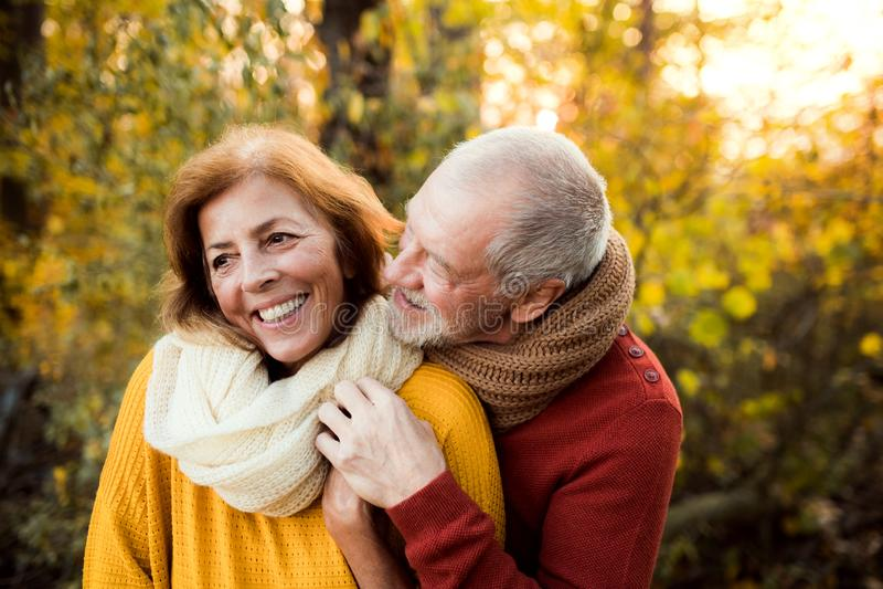 Un couple supérieur se tenant dans une nature d'automne au coucher du soleil, étreignant photographie stock