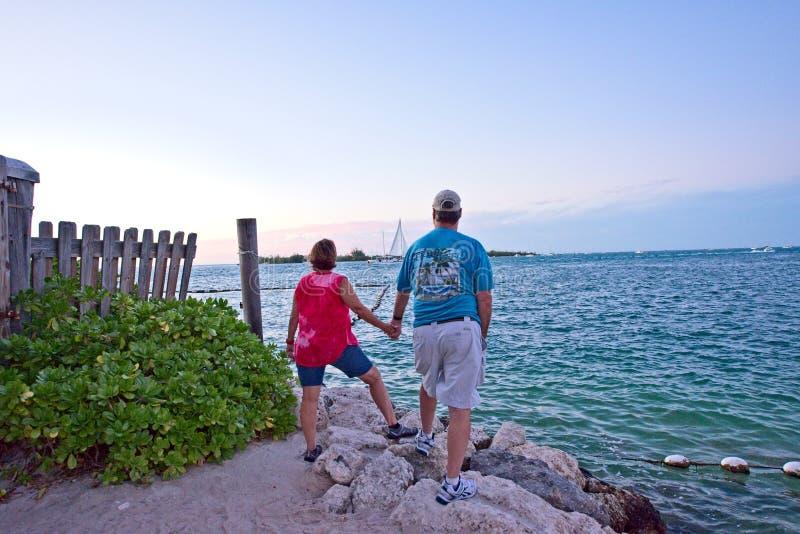Un couple supérieur tenant des mains tout en regardant fixement l'horizon sur l'Océan Atlantique à Key West, la Floride Etats-Uni photographie stock libre de droits