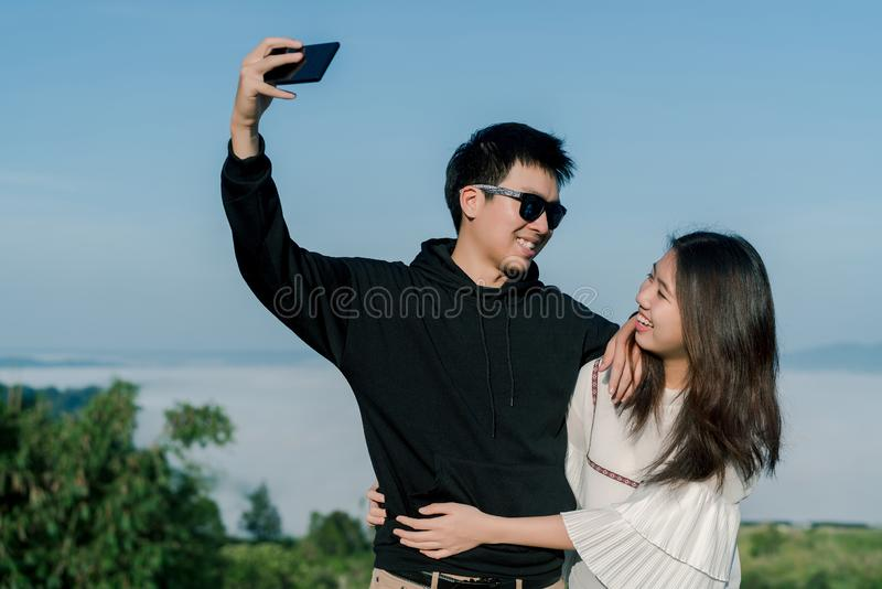 Un couple sur dater des selfies de prise ensemble par le smartphone avec la vue sup?rieure de la colline dans le backgroud Hommes image stock