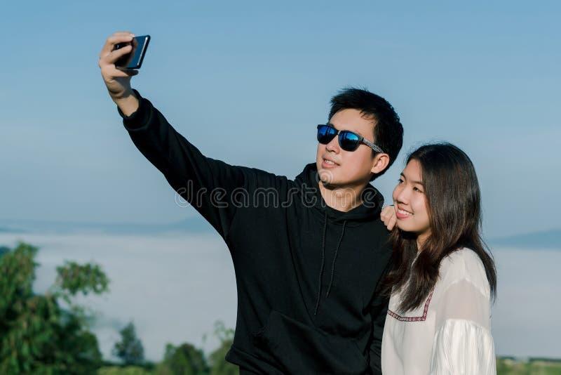 Un couple sur dater des selfies de prise ensemble par le smartphone avec la vue sup?rieure de la colline dans le backgroud E images stock
