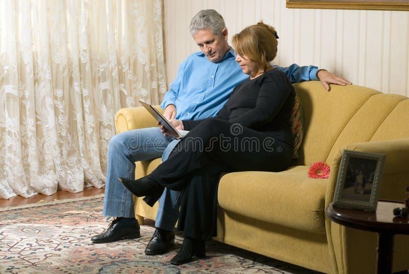 Un couple sur un divan avec une photo Album-Horizontale photo libre de droits
