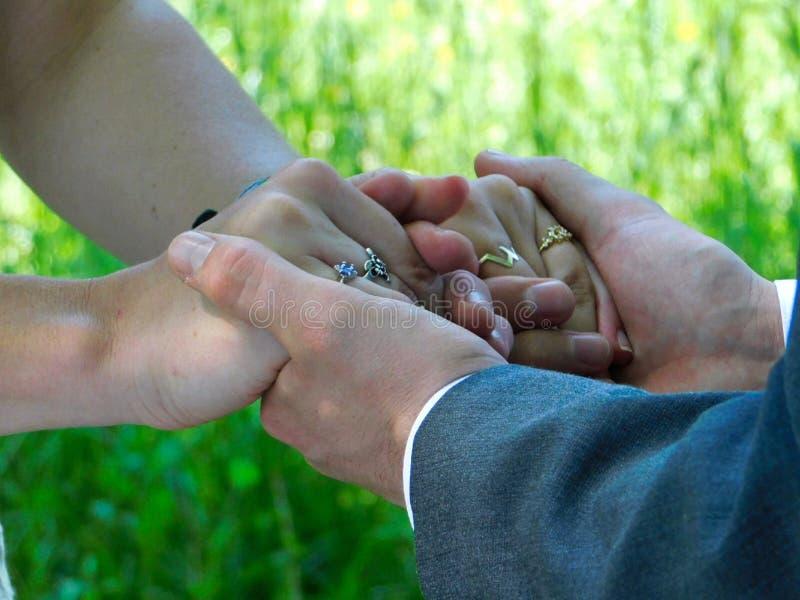 Un couple tenant des mains pendant un mariage extérieur images libres de droits