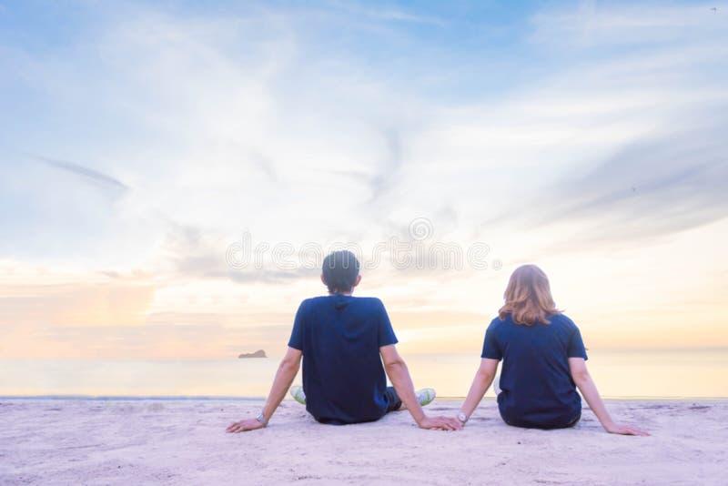 Un couple tenant la main et se voyant sur la plage avec le fond de ciel bleu image stock