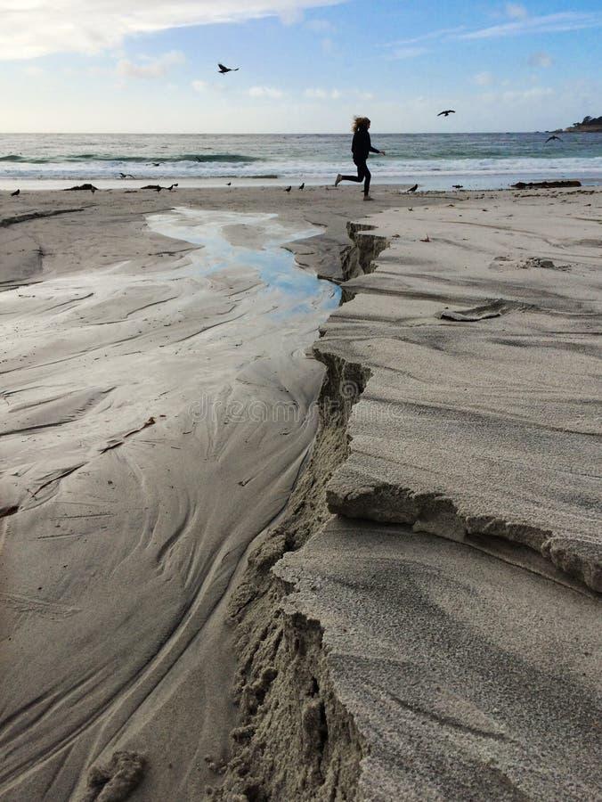 Un coureur femelle se silhouette le long du Pacifique avec une plage architecturale stupéfiante image stock