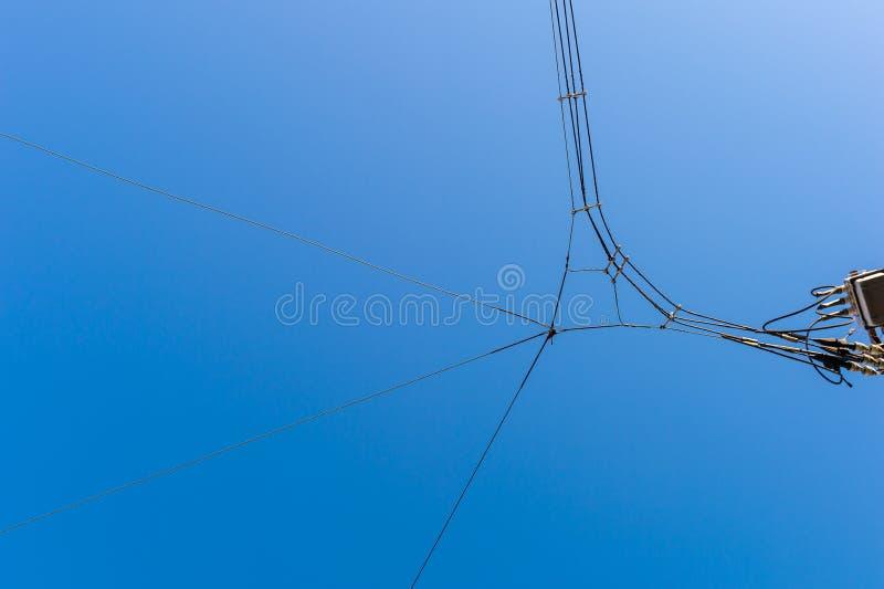 Un courrier électrique avec des fils avec le fond bleu de ciel nuageux images stock