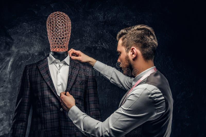 Un couturier vérifiant la qualité d'un costume d'hommes élégants faits sur commande dans un studio foncé de tailleur photo libre de droits