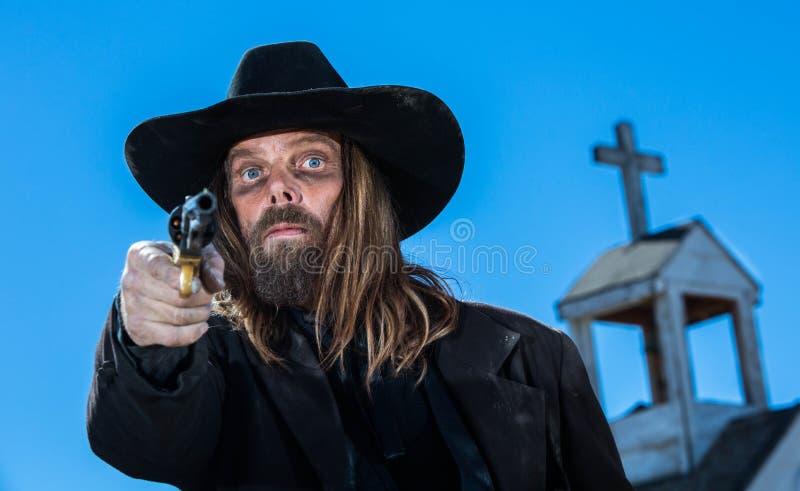 Un cowboy sérieux avec une arme à feu photographie stock