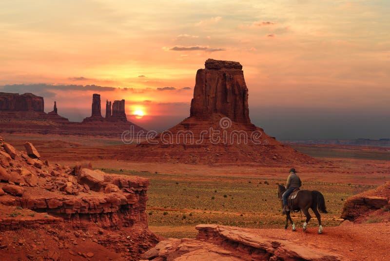 Un cowboy su un cavallo al tramonto nel parco tribale della valle del monumento in confine dell'Utah-Arizona, U.S.A. immagini stock libere da diritti