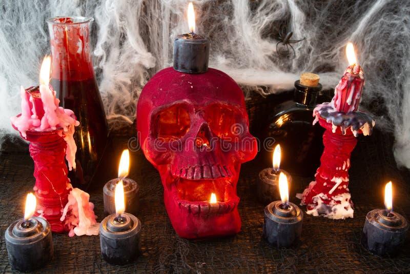 Un cráneo rojo del terciopelo rodeado por los candeleros rojos del terciopelo con dos velas rojas largas casi quema Dispersado al imágenes de archivo libres de regalías