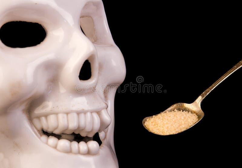 Un cranio e un cucchiaio di zucchero su un fondo nero fotografie stock