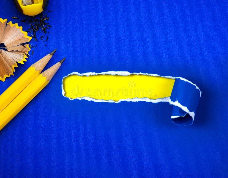 Un crayon jaune sur le papier bleu déchiré et l'espace pour le texte avec le YE photos stock