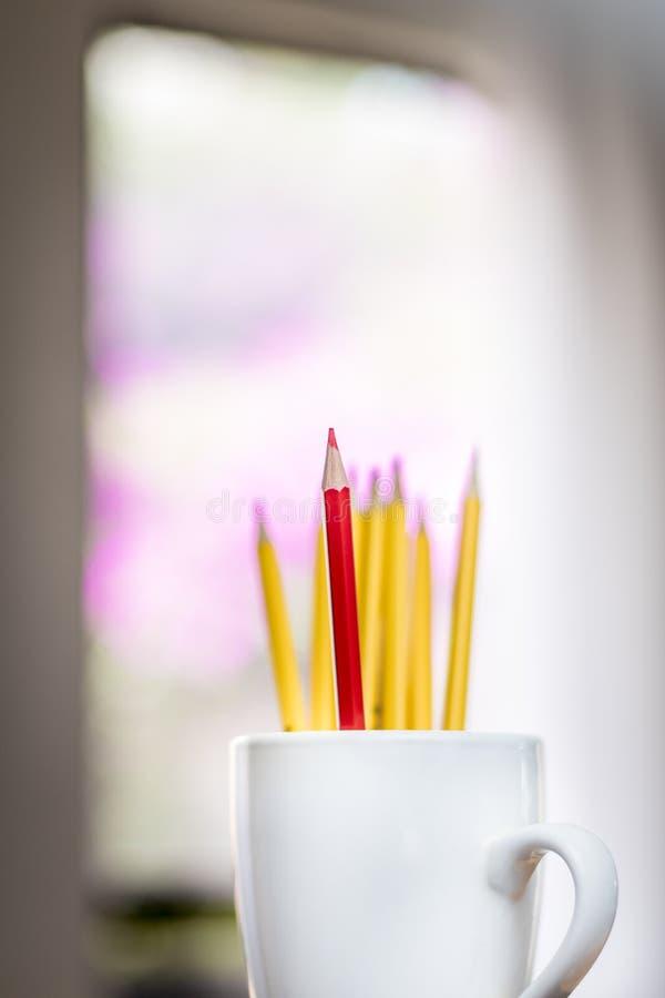Un crayon rouge solitaire devant un groupe de crayons jaunes dans une tasse blanche image libre de droits