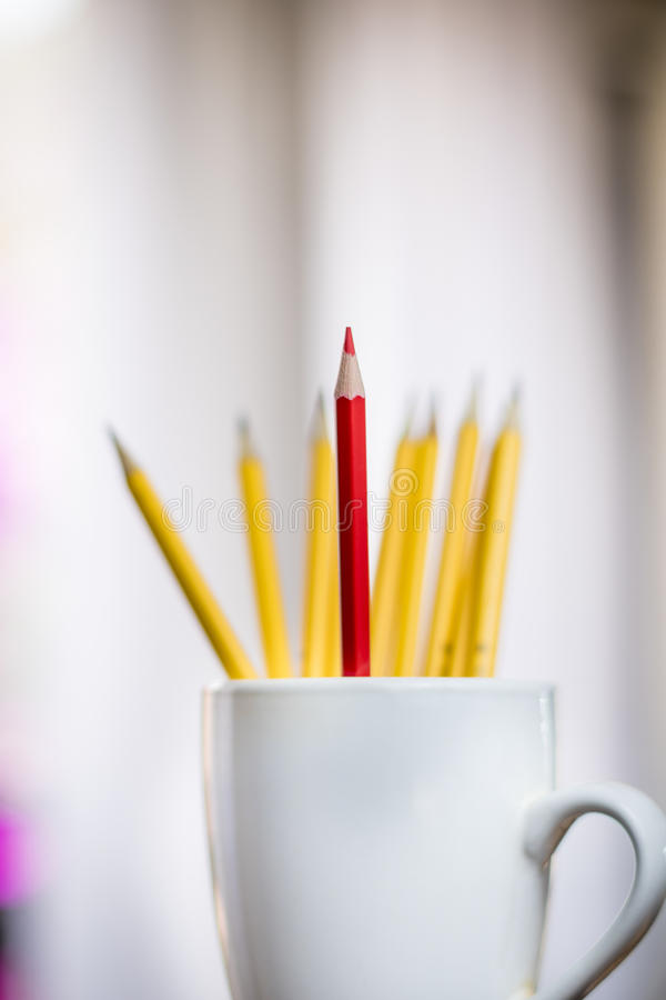 Un crayon rouge solitaire devant un groupe de crayons jaunes dans une tasse blanche image stock