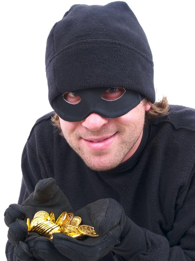 Un criminal enmascarado con oro imagen de archivo libre de regalías