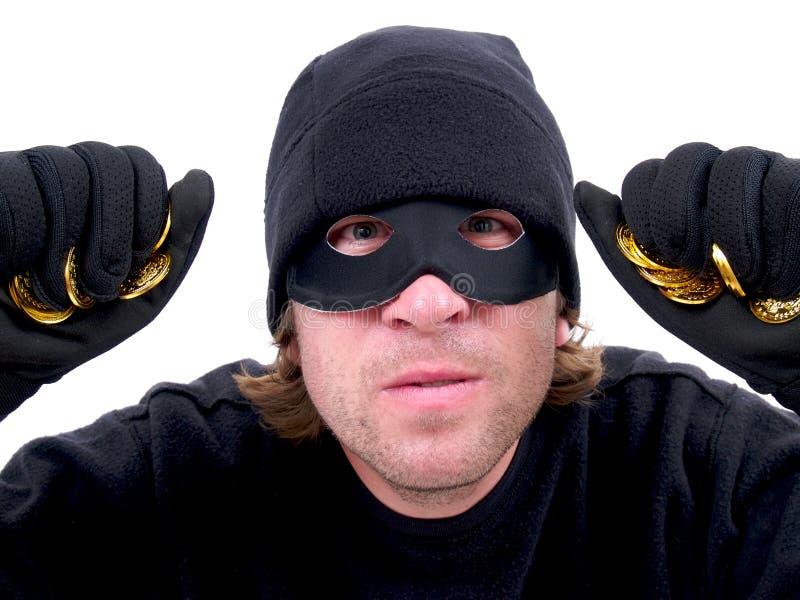 Un criminal enmascarado con oro foto de archivo libre de regalías