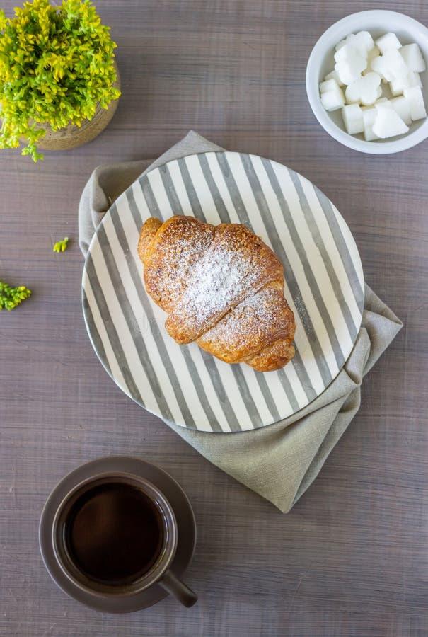 Un croissant et un café sur un fond gris Les fleurs Petit d?jeuner images libres de droits