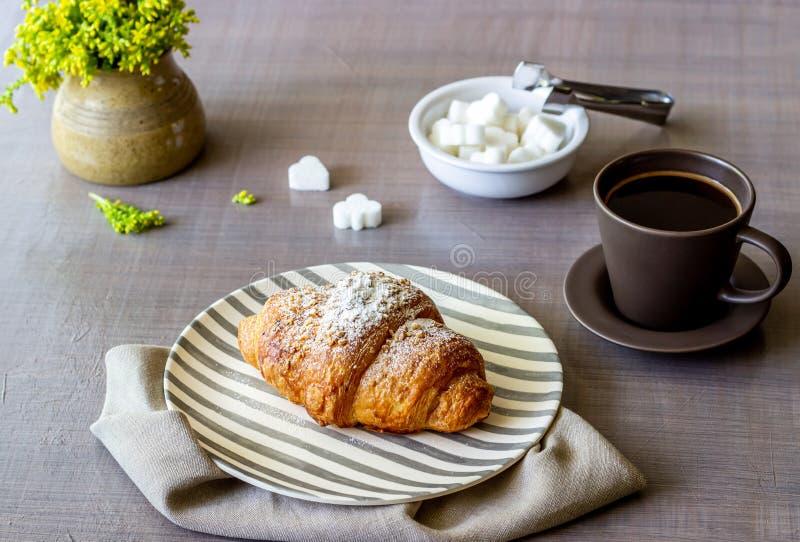 Un croissant et un café sur un fond gris Les fleurs Petit d?jeuner photos stock