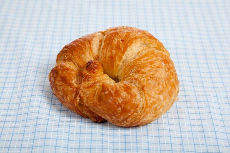 Un croissant su una tovaglia blu del percalle fotografia stock libera da diritti