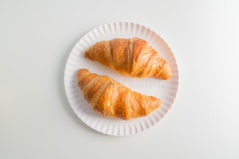 Un croissant sul piatto, fondo bianco di due pianure della tavola fotografia stock