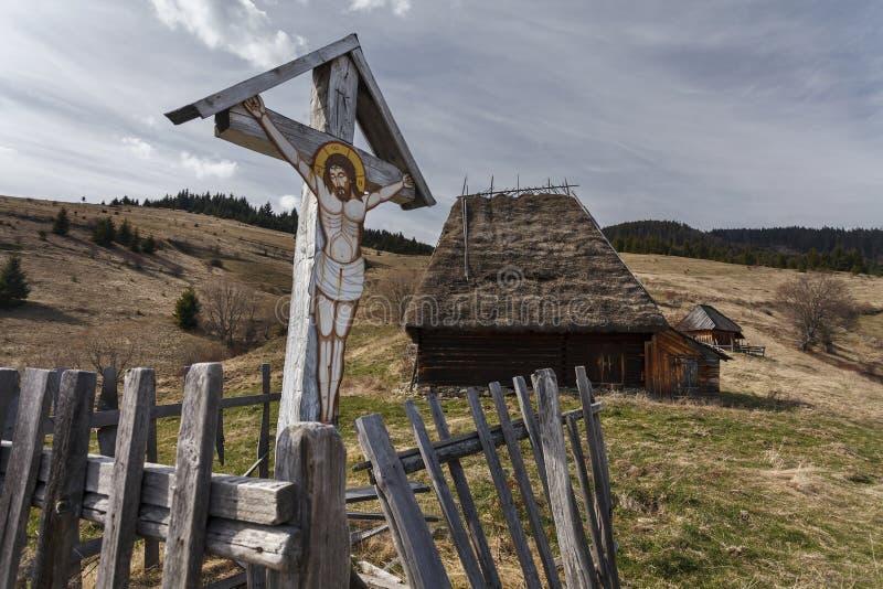 Un crucifix avec l'image du Christ sur une croix en bois près d'un vieux traditionnel photographie stock libre de droits