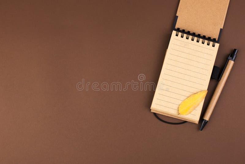 Un cuaderno abierto para las notas sobre un fondo marrón Espacio libre para el texto Hojas de la atmósfera y del amarillo del oto foto de archivo