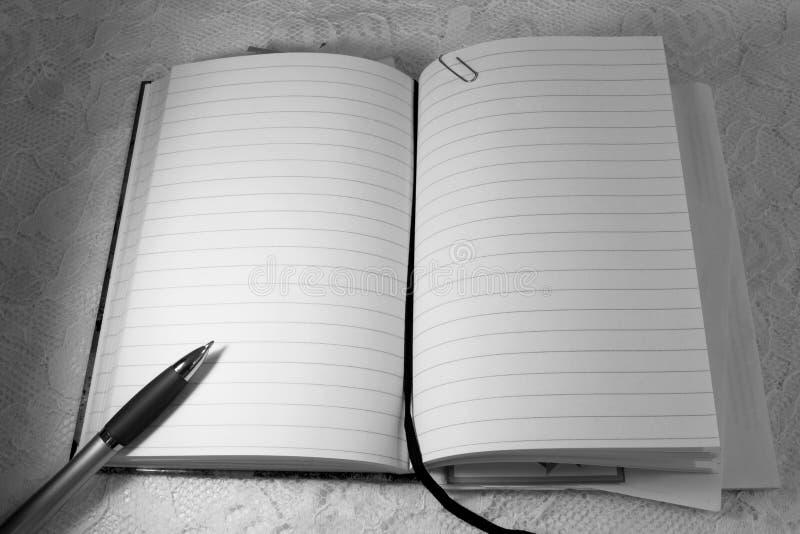 Un cuaderno abierto y un lápiz del bolígrafo imagenes de archivo