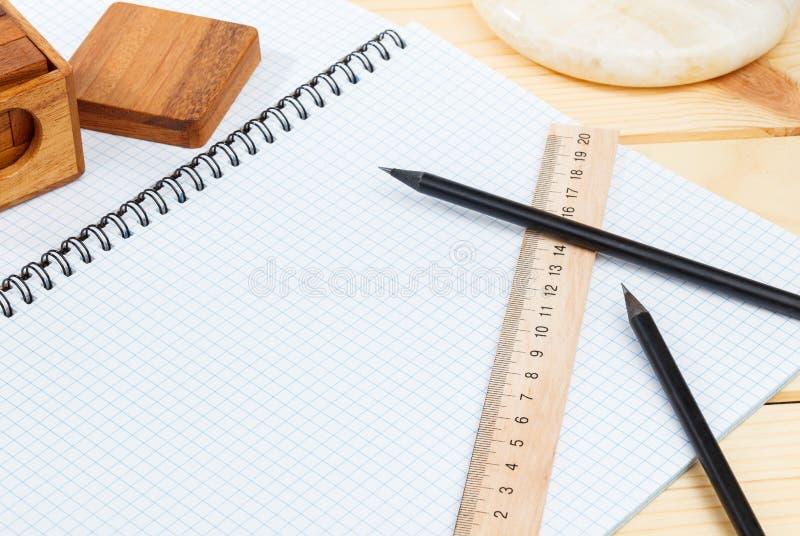 Un cuaderno abierto y una regla con dos lápices y un rompecabezas en un fondo de madera imagenes de archivo