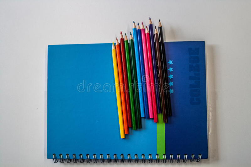 Un cuaderno con muchos creyones coloridos en él que pone en el blanco imágenes de archivo libres de regalías