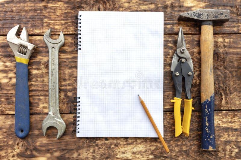 Un cuaderno en blanco con a mano las herramientas rodeadas un lápiz en una vieja superficie de madera fotos de archivo libres de regalías