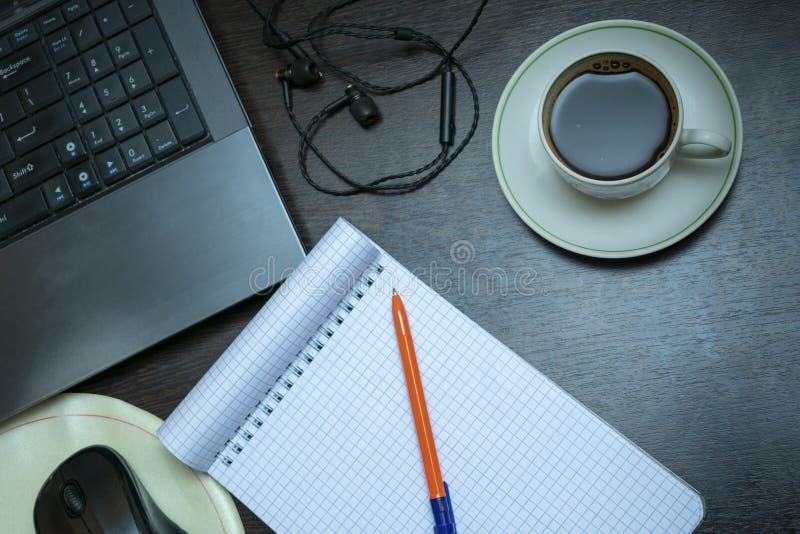 Un cuaderno limpio en la mesa, al lado del ordenador portátil, una taza de café, auriculares imagen de archivo