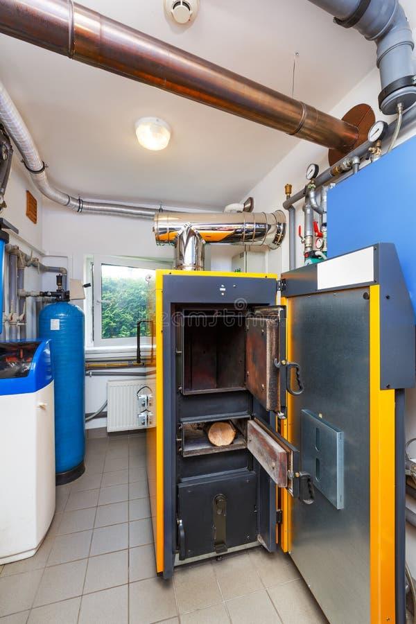 Un cuarto de caldera del hogar con una caldera en la leña, un barril; Val imagenes de archivo