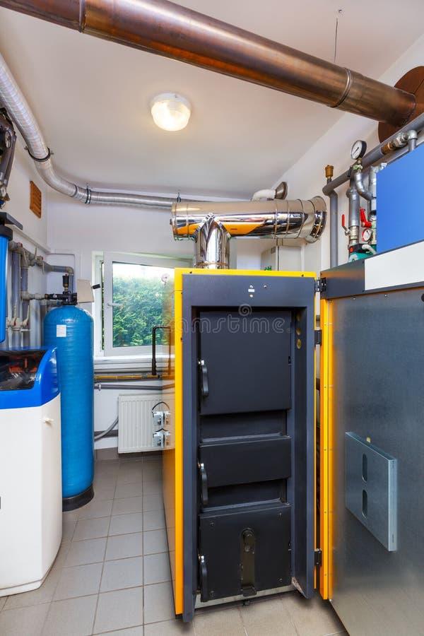 Un cuarto de caldera del hogar con una caldera en la leña, un barril; Val foto de archivo libre de regalías