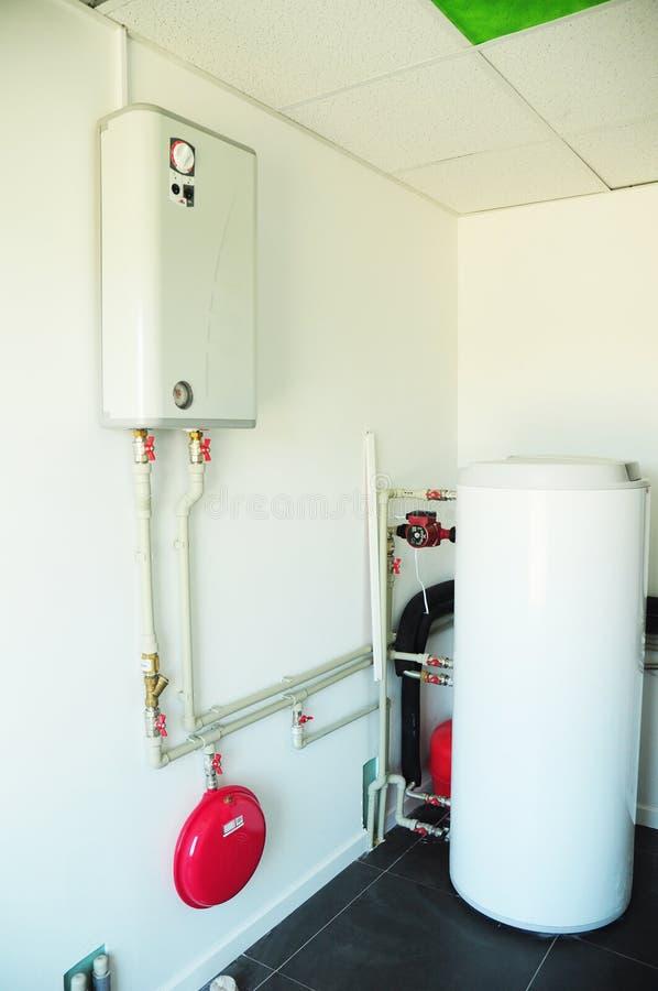 Un cuarto de caldera nacional del hogar con una nueva caldera de gas moderna, un circuito de agua caliente eléctrico de calefacci foto de archivo libre de regalías